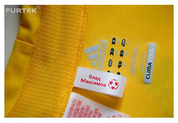Пришивная этикетка с именем ребенка пришитая к желтой футболке
