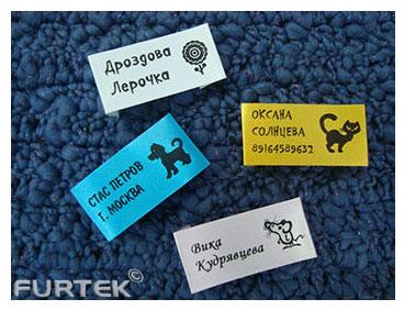 Четыре пришивные этикетки с именами детей лежат на синем фоне