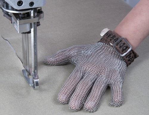 Рука в кольчужной перчатке удерживает ткань в то время как раскроечная машина режет ткань