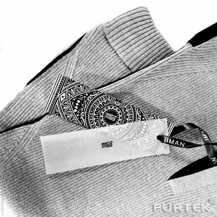 бирки на синих джинсах прикреплены веревочным биркодержателем за помочь