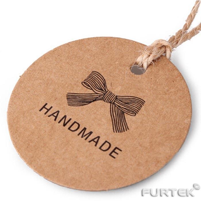 Картонная вырубная бирка с круглым отверстием из картона и надписью handmade на веревочном дрежателе