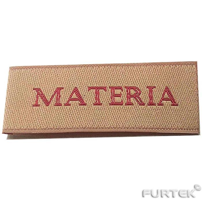 жаккардовая этикетка золотистого цвета с малиновой надписью materia прямоугольной формы без подгиба.