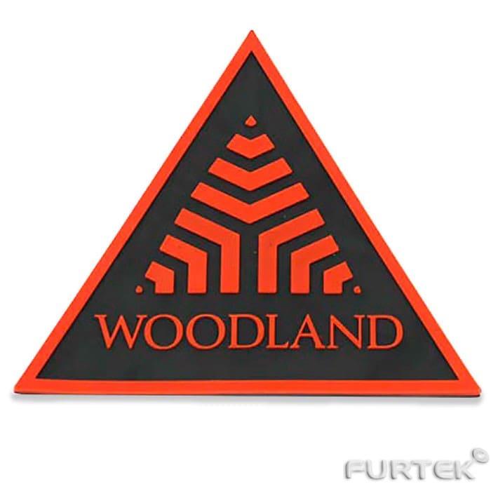 жаккардовая этикетка WoodLand в виде треугольника с оранжевым орнаментов на черном фоне