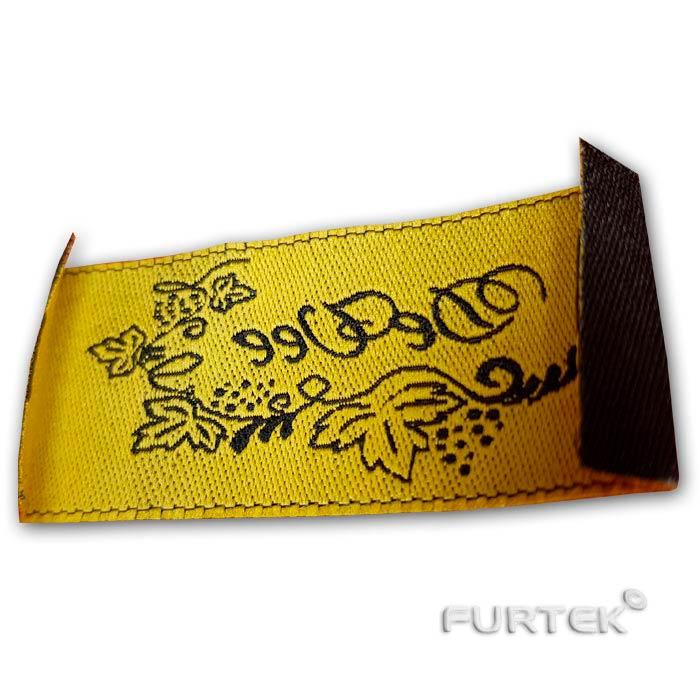 Жаккардовая этикетка черная, золотой текст, вид с обратной стороны под наклоном, фото