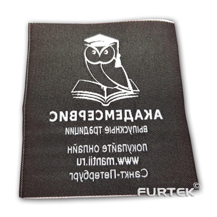 Жаккардовая этикетка белая с черным логотипом, вид с обратной стороны, фото
